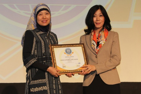 (kiri) General Manager Honda Customer Care Center AHM Istiyani Susriyati, menerima penghargaan Contact Center Service Excellence Award 2014 yang diserahkan oleh (kanan) CEO Carre CCSL Yuliana Agung di Hotel Mulia, Jakarta (3/4).